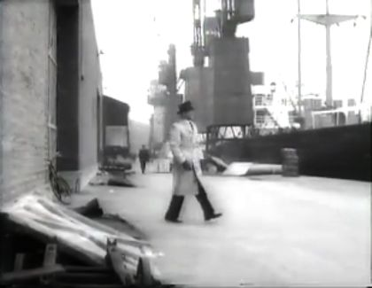 Extract from a Black and White film showing a man walking from a warehouse towards the quay side and a moored ship.