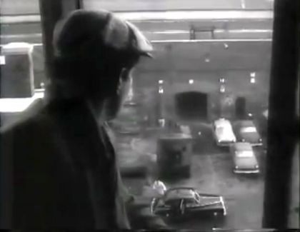 Extract from a Black and White film showing a crane operator overlooking the London Docks entrance.