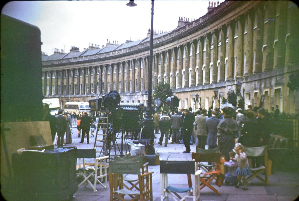 Wide angle shot of the film crew, together with others 'on set' during the filming of The Wrong Box against part of the Royal Crescent, Bath.