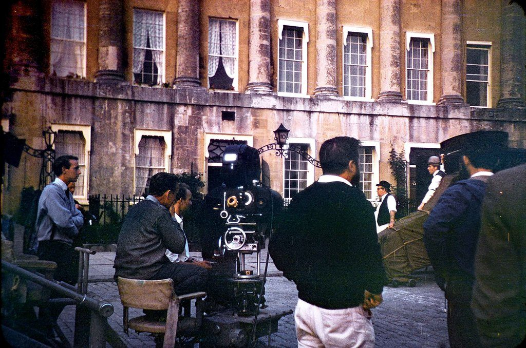 The rear view of some crew together with camera man and camera watching some cast against the back drop of a portion of the Royal Crescent, Bath.