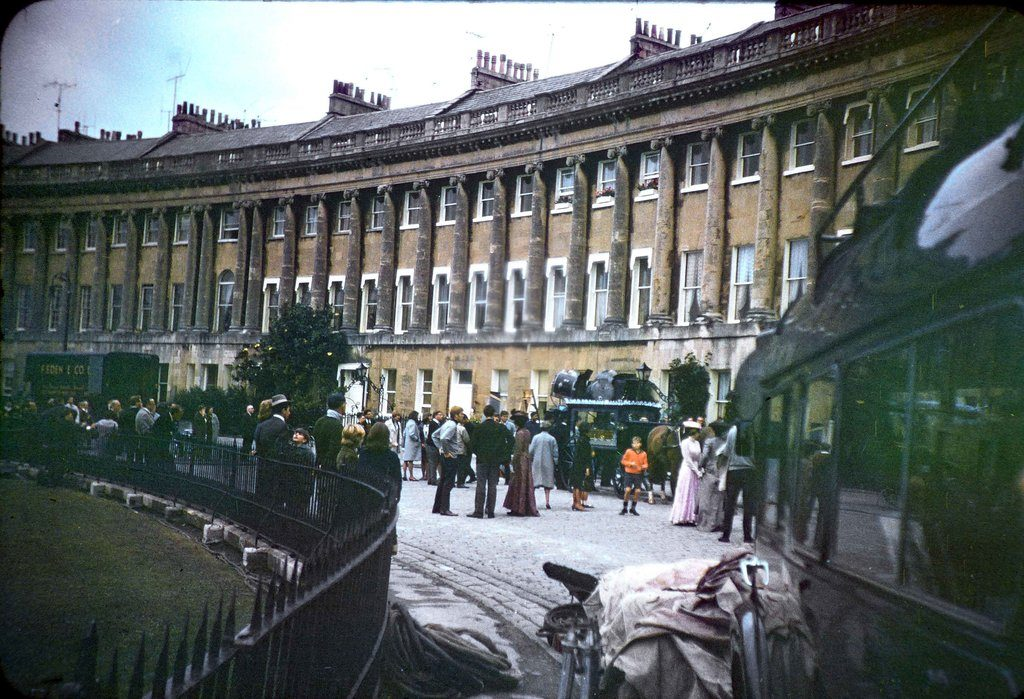 A wide angle shot of the film crew, together with others 'on set' during the filming of The Wrong Box against part of the Royal Crescent, Bath. Filmed from the right hand side.