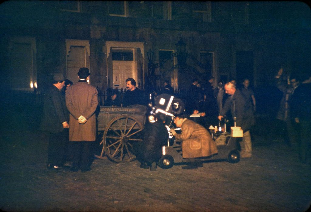 A close up of The film crew, film camera, some cast together with others 'on set' during the filming of The Wrong Box against part of the Royal Crescent, Bath.