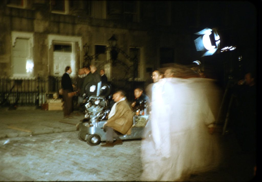 A close up of the film crew, film camera, some cast together with others 'on set' during the filming of The Wrong Box against part of the Royal Crescent, Bath. The white apparition is John Mills moving across during a limited time exposure.